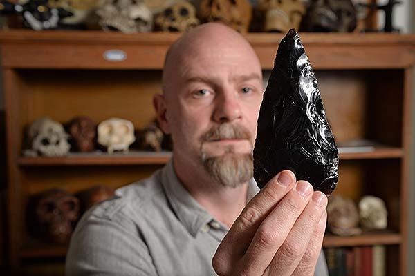 Daniel Adler presenta una hacha de mano, muestra de la creatividad tecnológica humana.